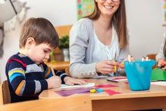 Preschool Teacher with Children at Kindergarten - Creative Art Class. Kindergarten teacher helping kids. Mother with her children having creative and fun time stock photography