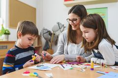 Preschool Teacher with Children at Kindergarten - Creative Art Class. Kindergarten teacher helping kids. Mother with children having creative and fun time stock photos
