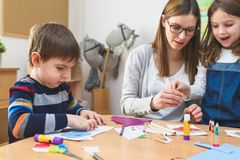 Preschool Teacher with Children at Kindergarten - Creative Art Class. Kindergarten teacher helping kids. Mother with children having creative and fun time royalty free stock photo