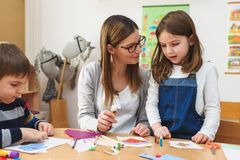 Preschool Teacher with Children at Kindergarten - Creative Art Class. Kindergarten teacher helping kids. Mother with children having creative and fun time stock photo