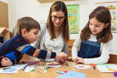 Preschool Teacher with Children at Kindergarten - Creative Art Class. Kindergarten teacher helping kids. Mother with children having creative and fun time stock photography