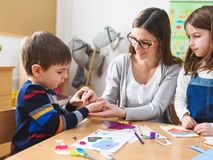 Preschool Teacher with Children at Kindergarten - Creative Art Class. Kindergarten teacher helping kids. Mother with her children having creative and fun time stock images