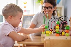 Preschool teacher with children playing with colorful didactic toys at kindergarten. Preschool teacher with children playing with colorful wooden didactic toys royalty free stock photography