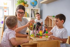 Preschool teacher with children playing with colorful didactic toys at kindergarten stock photography