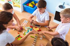 Preschool teacher with children playing with colorful didactic toys at kindergarten royalty free stock photos