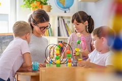 Preschool teacher with children playing with colorful didactic toys at kindergarten. Preschool teacher with children playing with colorful wooden didactic toys stock images
