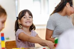 Preschool teacher with children playing with colorful wooden didactic toys at kindergarten. Kindergarten Teacher Supports Children in Educational Game Play royalty free stock image