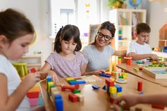 Preschool teacher with children playing with colorful wooden didactic toys at kindergarten. Kindergarten Teacher Supports Children in Educational Game Play stock photo
