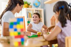 Preschool teacher with children playing with colorful didactic toys at kindergarten stock image