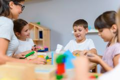 Preschool teacher with children playing with colorful didactic toys at kindergarten stock photos
