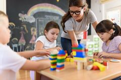 Preschool teacher with children playing with colorful wooden didactic toys at kindergarten. Kindergarten Teacher Supports Children in Educational Game Play royalty free stock photo