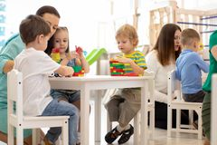 Preschool teacher with children playing with colorful wooden educational toys at kindergarten. Preschool teacher with kids playing with colorful wooden stock photo