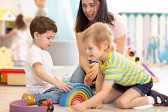 Preschool teacher with children playing with colorful wooden toys at kindergarten. Preschool teacher with children playing on floor with colorful wooden toys at stock photography