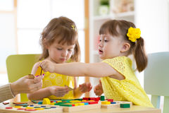 Preschool teacher and children playing with educational sorter toys in classroom. Preschool teacher and children play with educational sorter toys in classroom royalty free stock photo