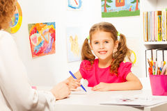Preschool teacher helping pupil with class work Stock Image
