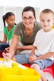Preschool teacher and kids. A happy preschool teacher and kids in classroom painting pictures Stock Photo