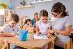 Preschool teacher looking at smart child at kindergarten. Preschool teacher looking at smart child learning to write and draw. Early education. Harnessing stock image