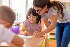 Preschool teacher looking at smart child at kindergarten. Preschool teacher looking at smart child learning to write and draw. Early education. Harnessing royalty free stock photos