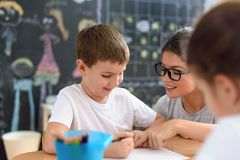 Preschool teacher looking at smart child learning to write and draw stock image