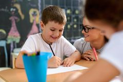 Preschool teacher looking at smart smiling boy at kindergarten. Preschool teacher looking at smart smiling boy that learning to write and draw. Early education stock photography