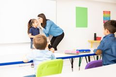 Preschool teacher playing a game in class. Pretty preschool teacher whispering in a pupil`s ear while playing a game in the classroom stock images