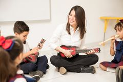 Preschool teacher playing the guitar in class. Fun female preschool teacher playing a guitar and teaching some music to her students royalty free stock photos