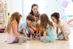 Preschool teacher plays with group of kids sitting on a floor at kindergarten stock images
