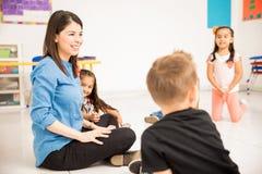 Preschool teacher and pupils having fun stock photo