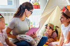 Preschool teacher reading a story to children at kindergarten. Mother reading to the children stock photo