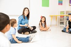 Preschool teacher sitting in the floor. Cute looking young women teaching her preschool students while making a circle and sitting in the classroom floor royalty free stock photography