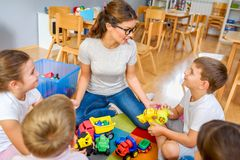 Preschool teacher talking to group of children sitting on a floor at kindergarten. Early education. Harnessing creativity and support royalty free stock image