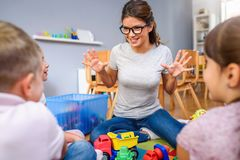 Preschool teacher talking to group of children sitting on a floor at kindergarten stock photos