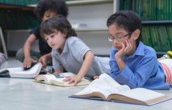 Preschool ucznie kłaść na podłodze i odpoczywają podbródek na ręce, czytają książkę w, bibliotece, pojęciu, uczenie i edukacji fotografia royalty free