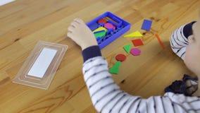 Preschooler που ερευνά τις γεωμετρικές μορφές, τις μορφές και τα χρώματα φιλμ μικρού μήκους