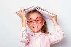 Preschooler девушки Ittle нося стекла держит открытую книгу на ее голове стоковая фотография