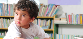 Preschooler. Boy sitting in a classroom and looking at camera Royalty Free Stock Image