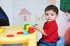 Preschooler adorável que joga com massa de pão colorida foto de stock