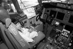 Preschooler in Airplane Cockpit. Preschooler having an opportunity of sitting in the pilot seat after a long flight stock photography