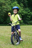 Preschooler and bike. 6 years old boy with bike and green apple royalty free stock image