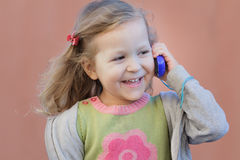 Preschooler blonde girl having fun during her dialogue by mobile phone stock image