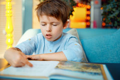 Preschooler boy reading book Stock Image