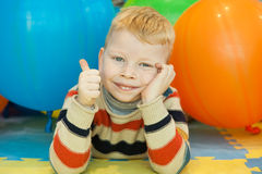 Preschooler Boy Show Thumb up. A little boy lying on the floor surrounded by colorful balloons Royalty Free Stock Photography