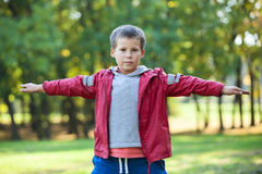 Preschooler boy standing with arms spread to the side in park Stock Images