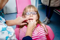 Preschooler child is at dentist office. Frightened sweet little girl with open mouth is at dentist office, dental care Royalty Free Stock Photography