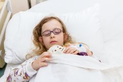 Preschooler child is lying sick on a bed in hospital room royalty free stock photography