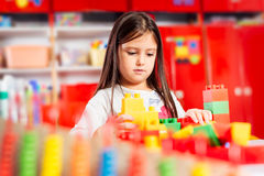 Preschooler child playing with colorful toy blocks. Stock Photos