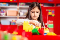 Preschooler child playing with colorful toy blocks. Stock Image