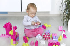 Preschooler child playing with colorful toy blocks Stock Images