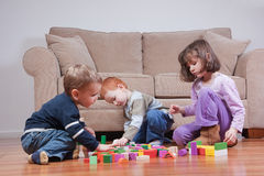 Preschooler children playing with toy blocks. Three preschooler kids playing with blocks Royalty Free Stock Photo