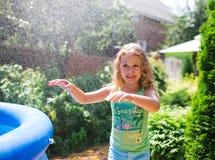 Preschooler cute girl playing with garden sprinkler. Summer outdoor water fun in the backyard. Stock Photos